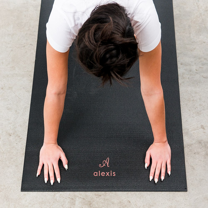 White woman with black hair in a bun wearing a white t-shirt doing a downward dog on a black personalised yoga mat