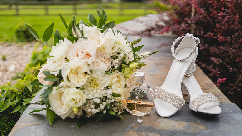 A wedding bouquet, bridal shoes and a bottle of Chanel perfume outside Oldwalls Gower wedding venue