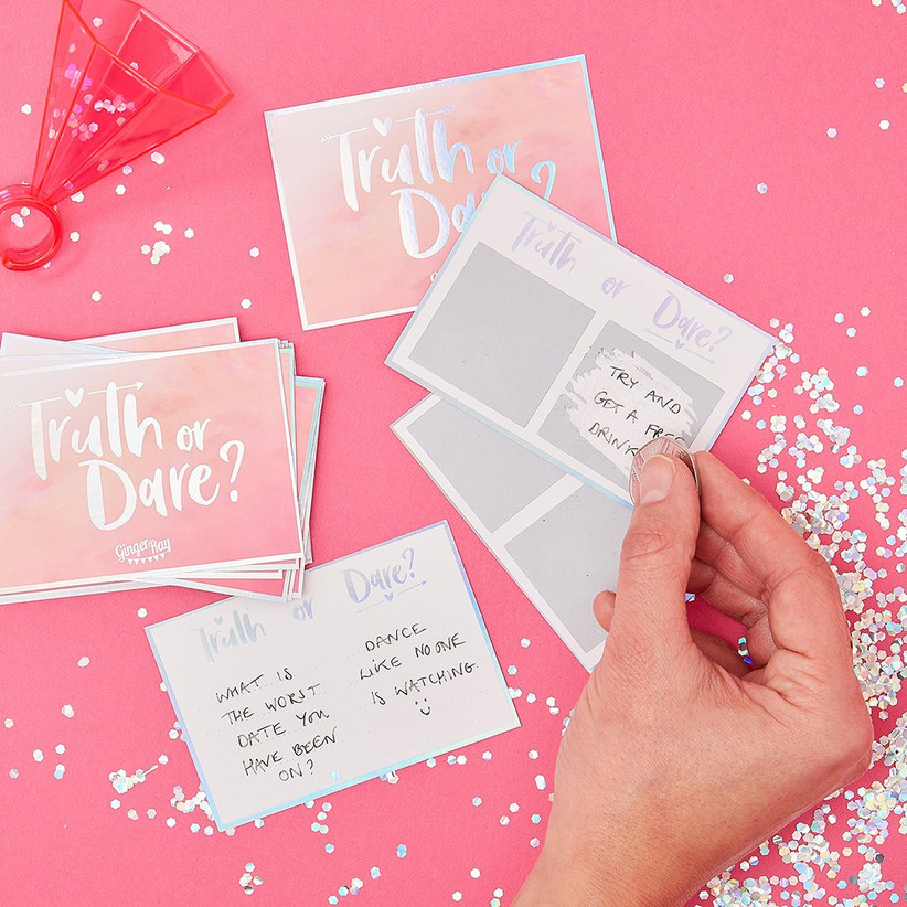 Truth or dare hen party cards on a pink sequin table