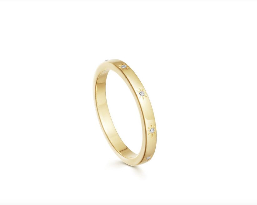 Yellow gold band studded with small diamonds with a star shape etched around each one