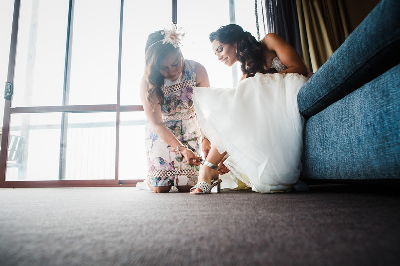 Woman helping her daughter put on her wedding shoes