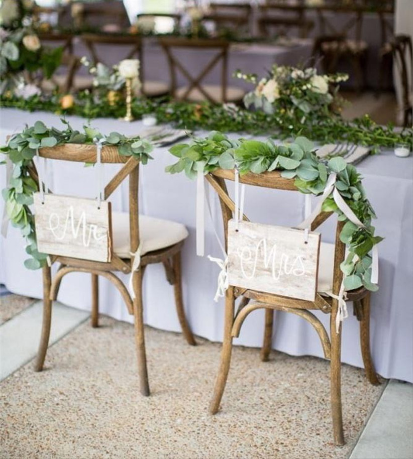wooden-wedding-chairs-with-greenery-on-them