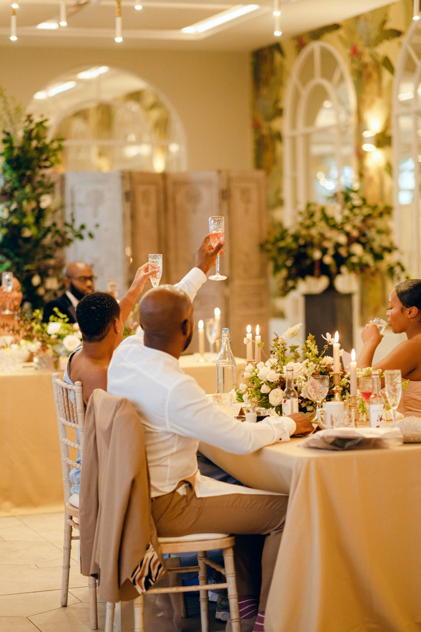 Wedding guests toasting the couple with glasses of champagne