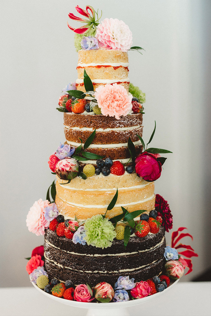 Four layered multi-flavour rustic wedding cake with flowers and fruit