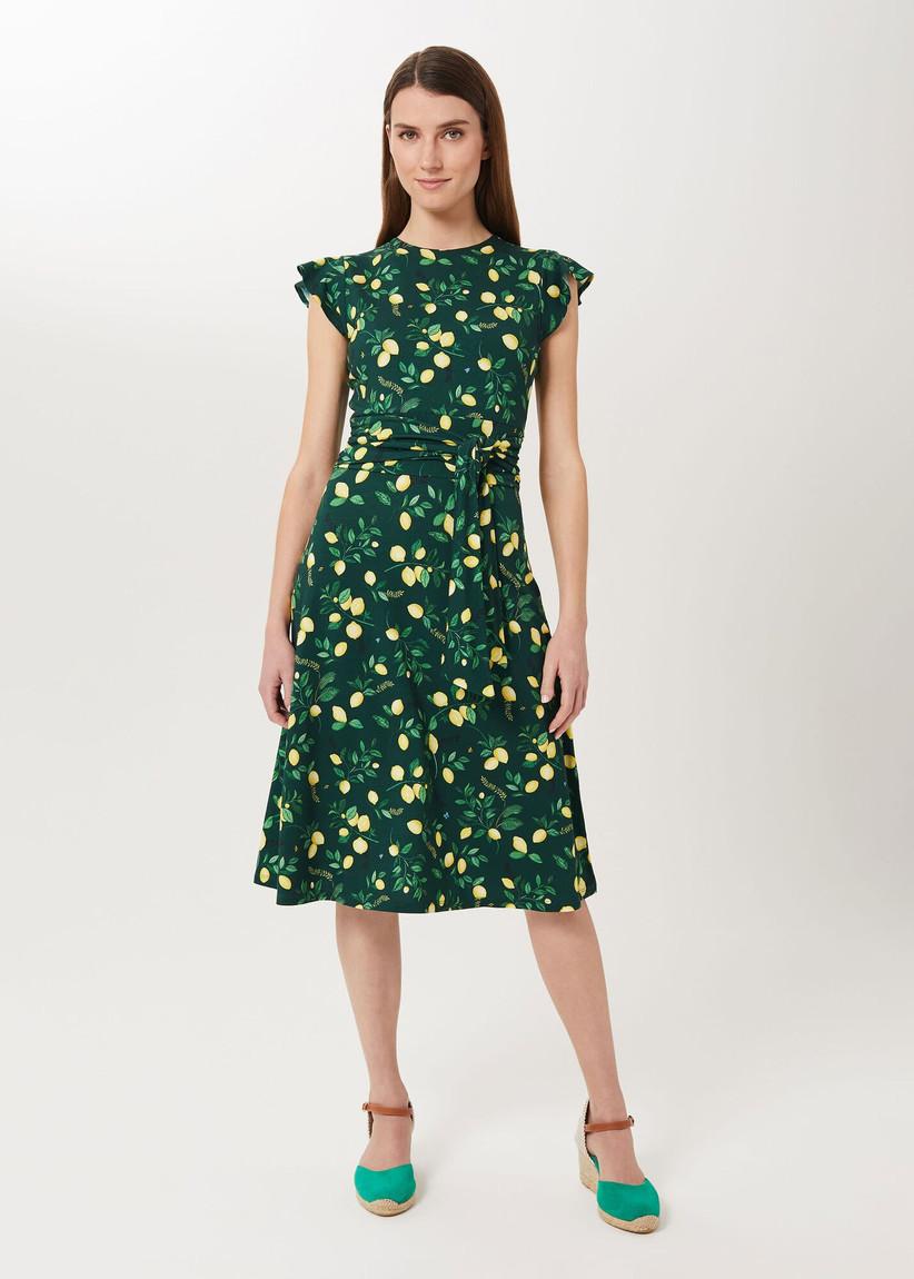 Girl wearing a green midi dress with lemon print