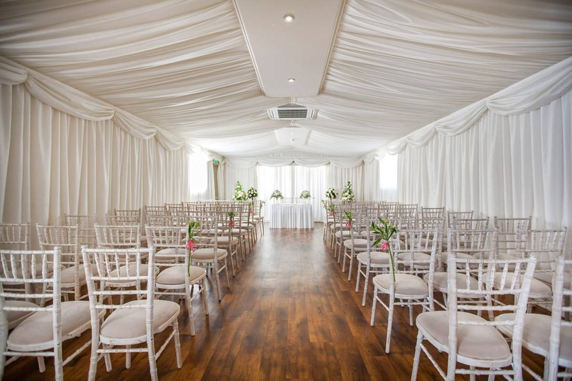 Wedding ceremony with white draped curtains and white chairs