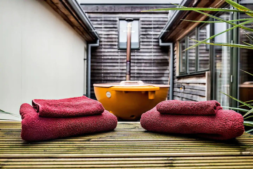 Outside decking with yellow hot tub and rolled up towels