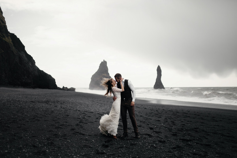 Newlywed woman and man kissing on a windy black sand beach