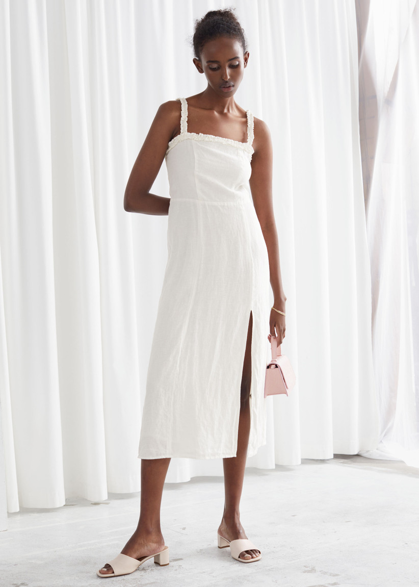 Girl wearing a simple ruched strap white dress holding a handbag