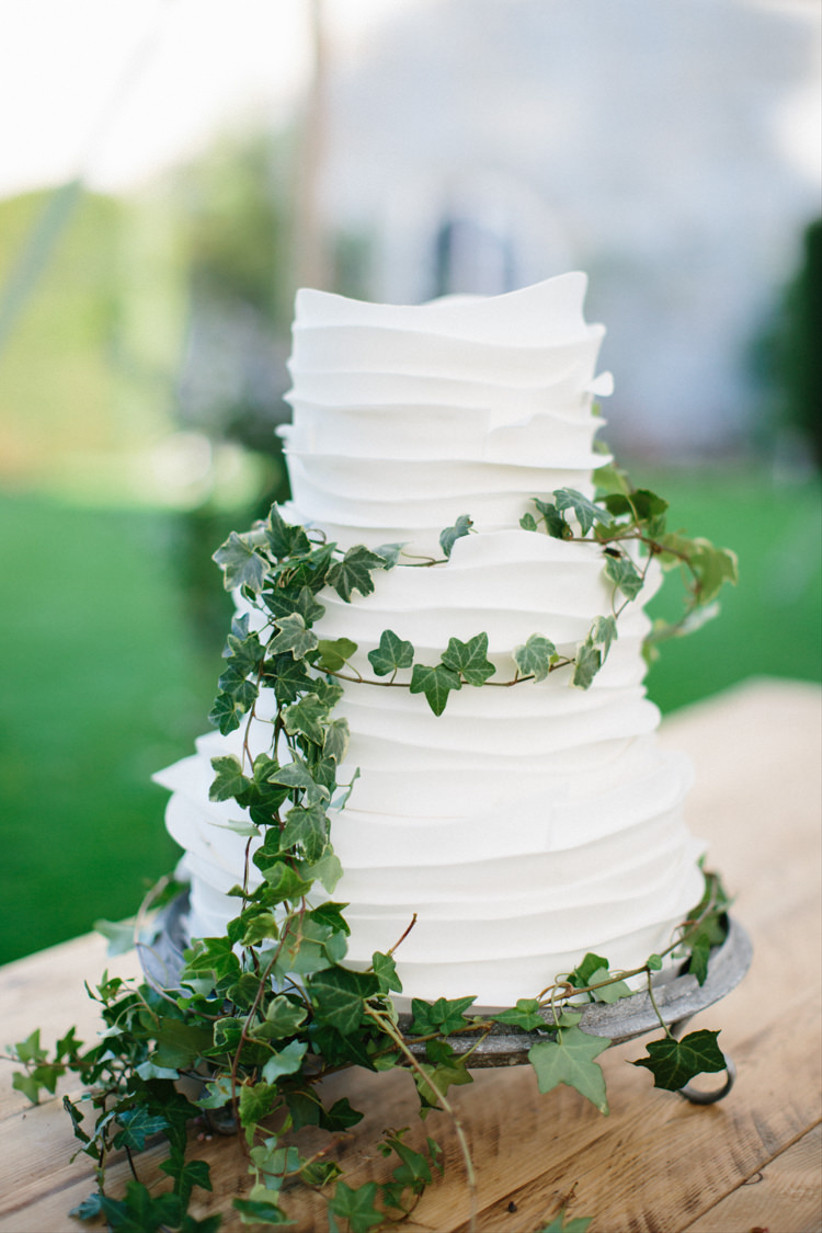 Rustic wedding cake with white icing and ivy
