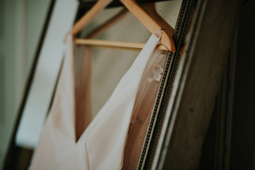 Close up of the top of Katherine's wedding dress hanging on a mirror