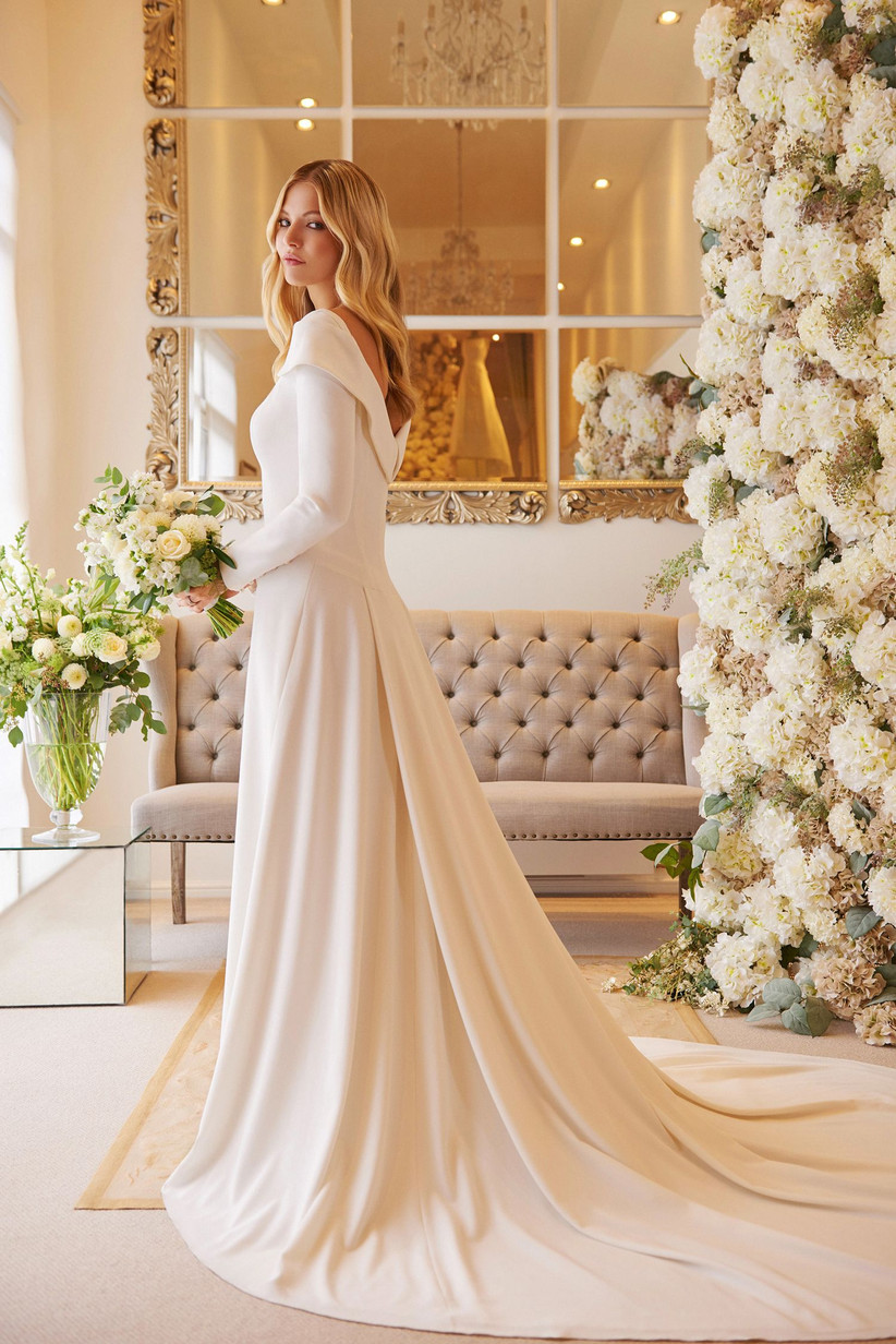 Model wearing a cuffed long sleeved wedding dress