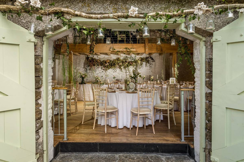 Barn doors open to reveal dining area with floral decorations