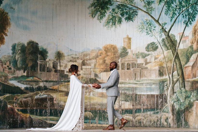 Bride and groom hold hands next to a large mural