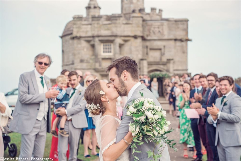 Bride and groom kiss outside a castle surrounded by wedding guests