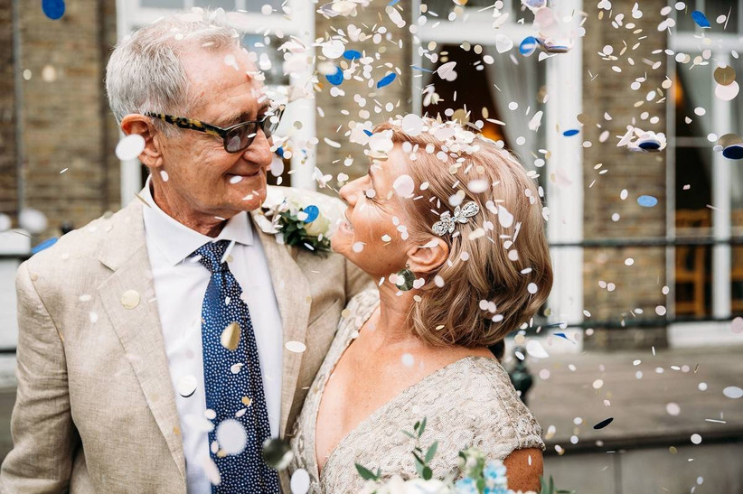 Bride and groom smile with confetti