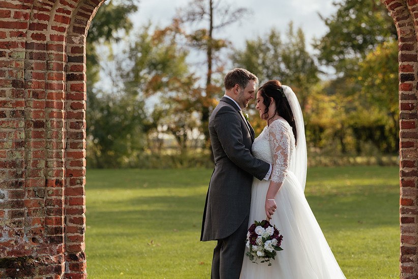Ben and Becky from the side in a red brick archway