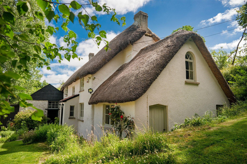 Outside view of a white cottage with a thatched roof