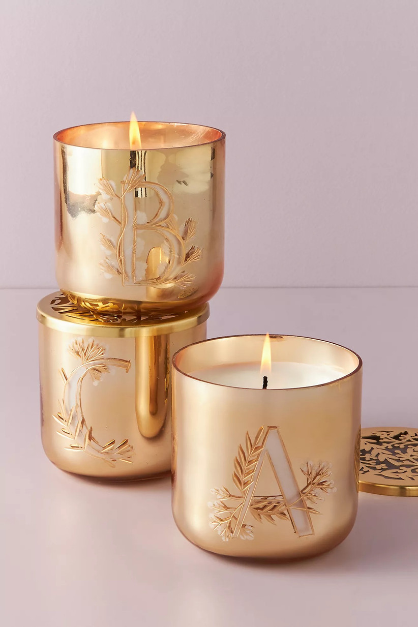 Three gold etched monogrammed candles featuring different engraved single letters