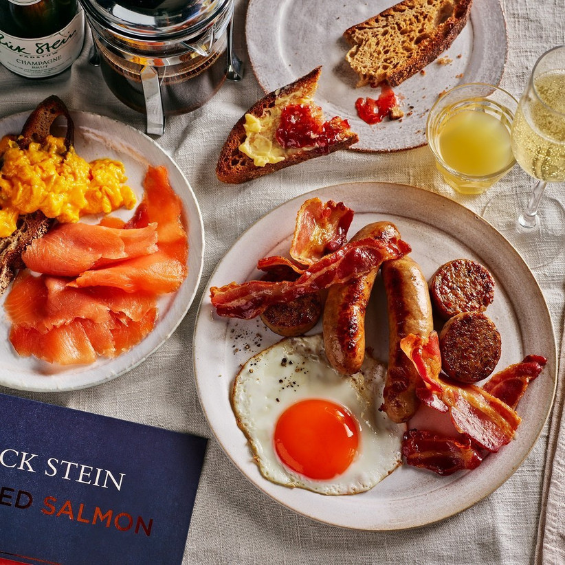 A fry up breakfast on a white plate next to a plate of toast, scrambled eggs and smoked salmon