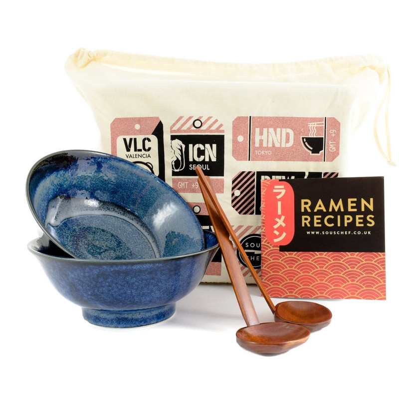 Two dark blue china ramen bowls stacked together next to two wooden ramen labels, a gift back and a ramen recipe booklet