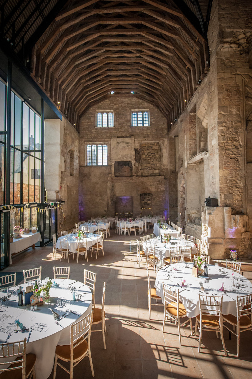 Interior of Gloucester Blackfriars Priory set up for a wedding, with stone walls and exposed brick contrasting with the pretty decorations