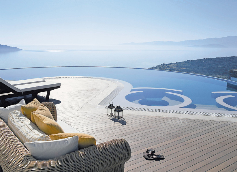 Sofa with yellow cushions on wooden decking next to an infinity pool
