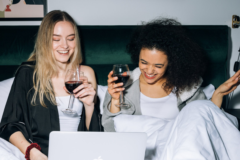 Girls laughing in bed with wine