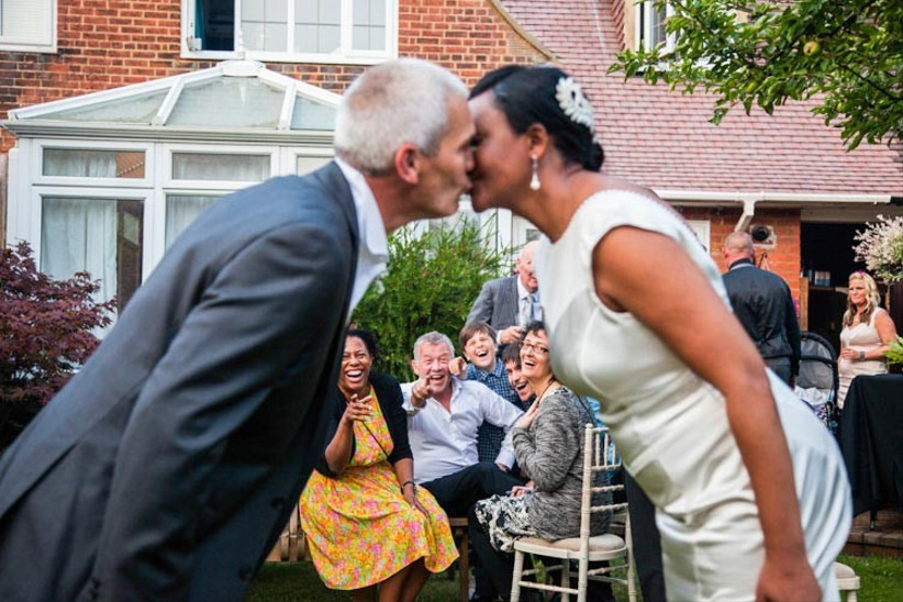 bride-and-groom-kissing-in-front-of-giggling-guests-2