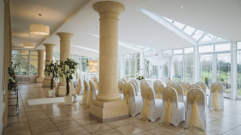 Wedding ceremony room with glass windows and white bow tied chairs