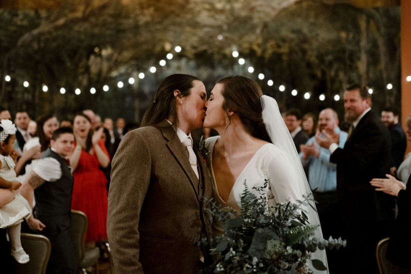Woman in a wedding dress kissing a woman in a suit with a cheering congregation behind them and fairy lights above