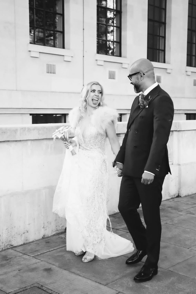 Black and white photo of a newlywed couple with a white bride with blonde hair sticking her tongue out at her groom wearing an embellished v-necked wedding dress with a white fur cape and simple bouquet