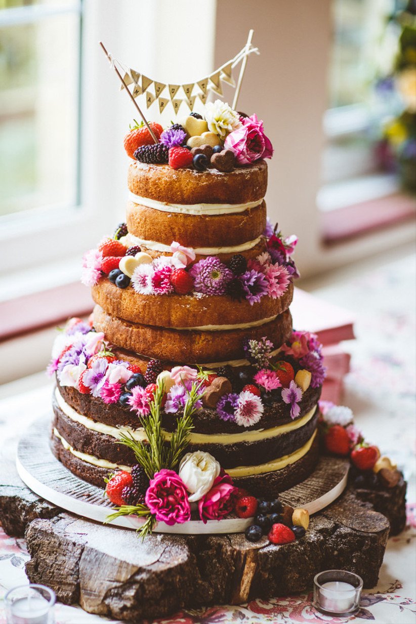Three tiered victoria sponge rustic wedding cake with flowers, fruit and bunting topper