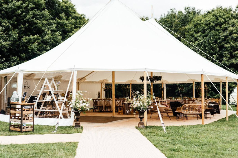 Wedding tipi decorated with wooden furniture and white flowers