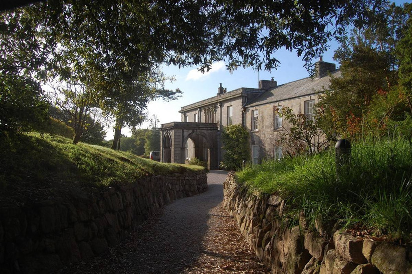 Outside view of a path leading up to a stone manor house