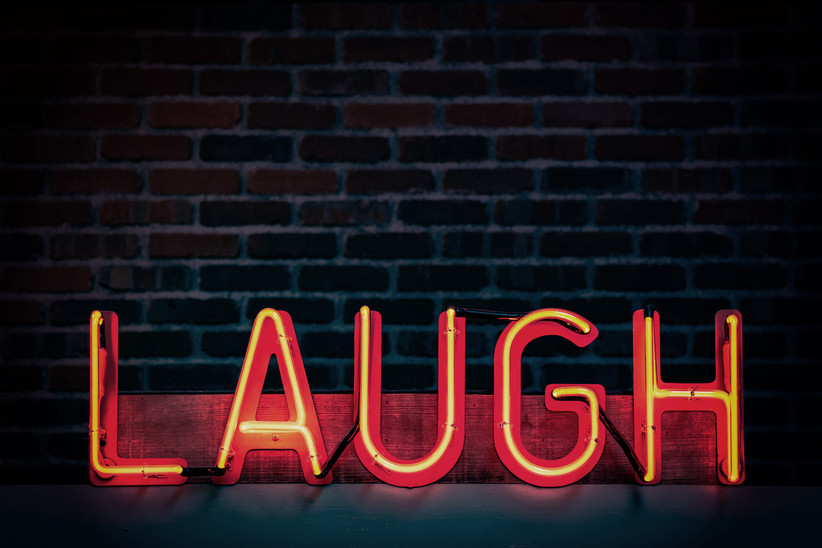 A neon orange laugh sign against a black wall background