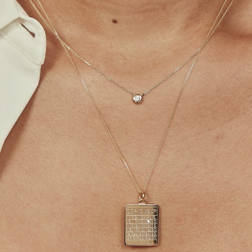 White woman wearing gold necklace with a calendar face and diamond stud on an important date