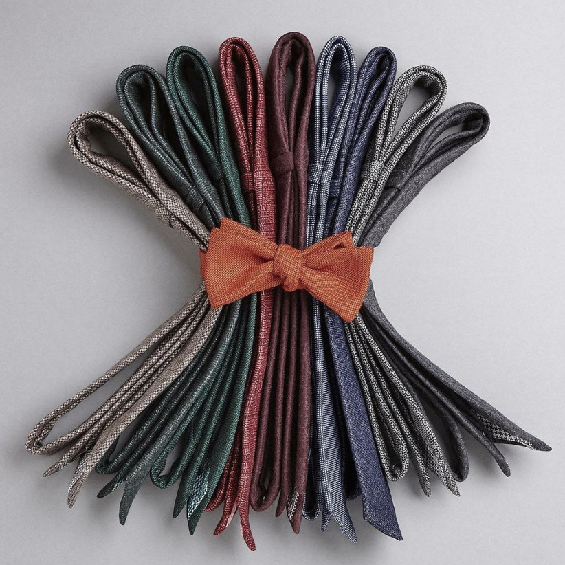 Assortment of different coloured ties secured together with an orange tie in the shape of a bow