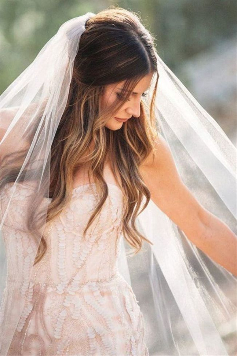 Model wearing a veil with a half up half down hairstyle
