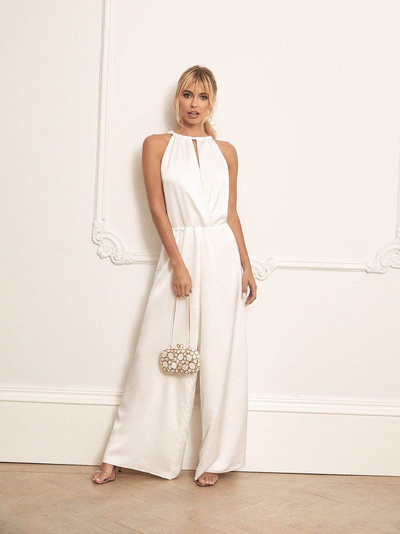 Girl wearing a white satin jumpsuit holding a clutch bag