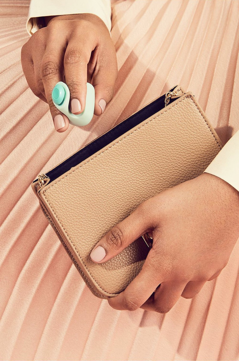 Woman holding a small handheld mint green vibrator between her fingers with the other hand holding a gold clutch bag