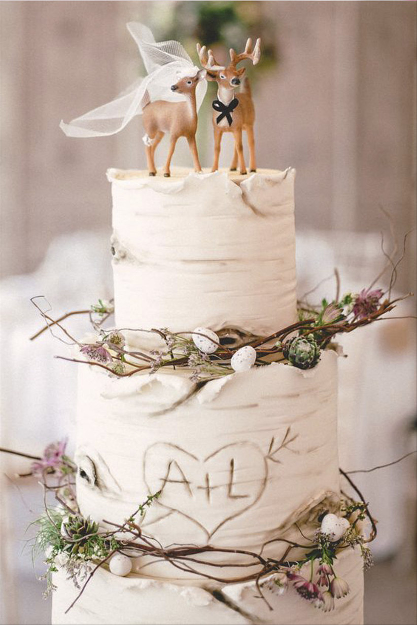 White rustic wedding cake with deer topper and branches