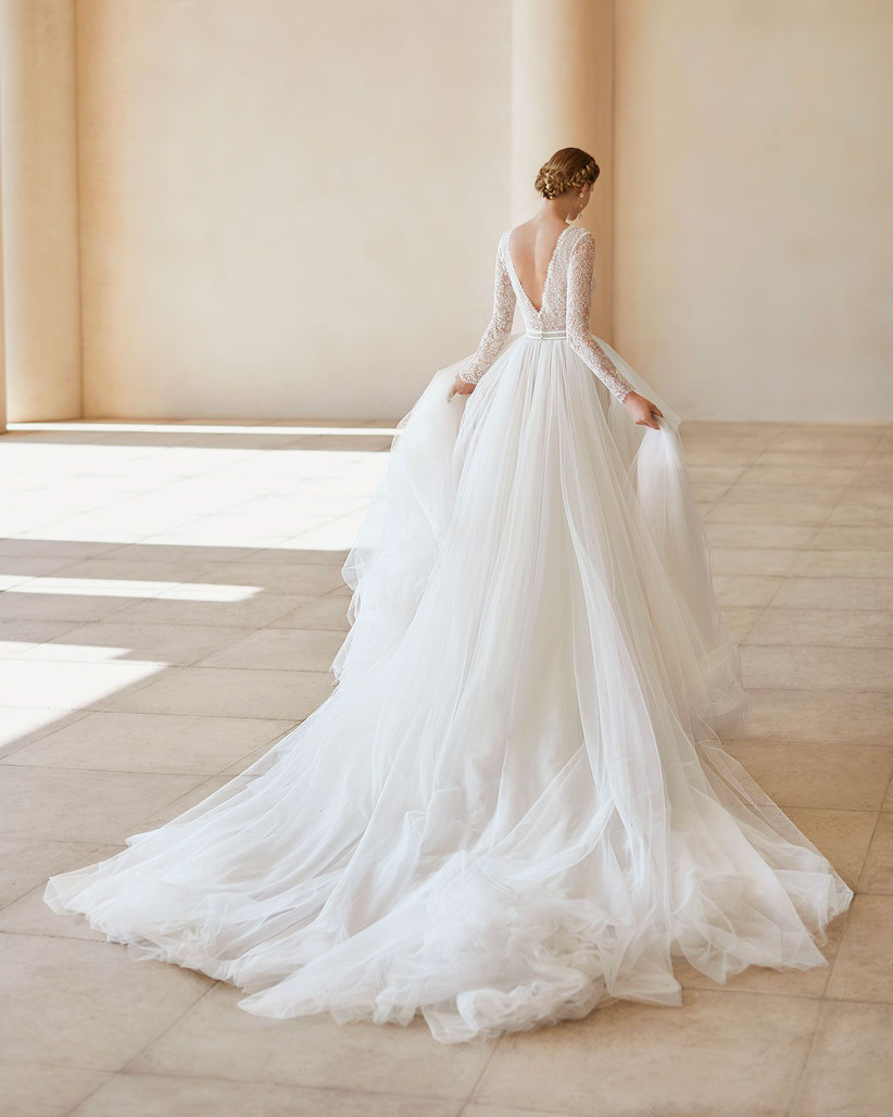 Model wearing a V neck lace long sleeved wedding dress