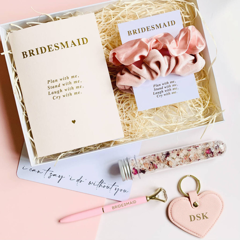 White gift box containing a white bridesmaid notebook, pink pen with a faux diamond on top, a set of pink silk scrunchies, a vial of Himalayan salt bath soak and a light pink leather monogrammed keyring