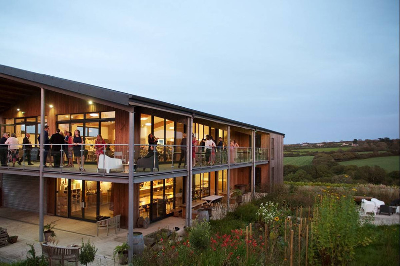 Outside view of a glass windowed building overlooking vineyards and fields