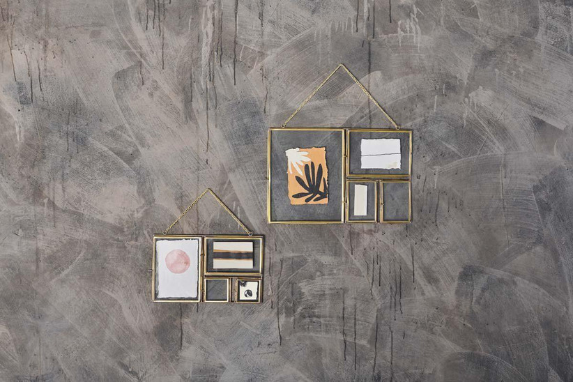Antique brass and glass picture frames hanging on a roughly painted grey wall