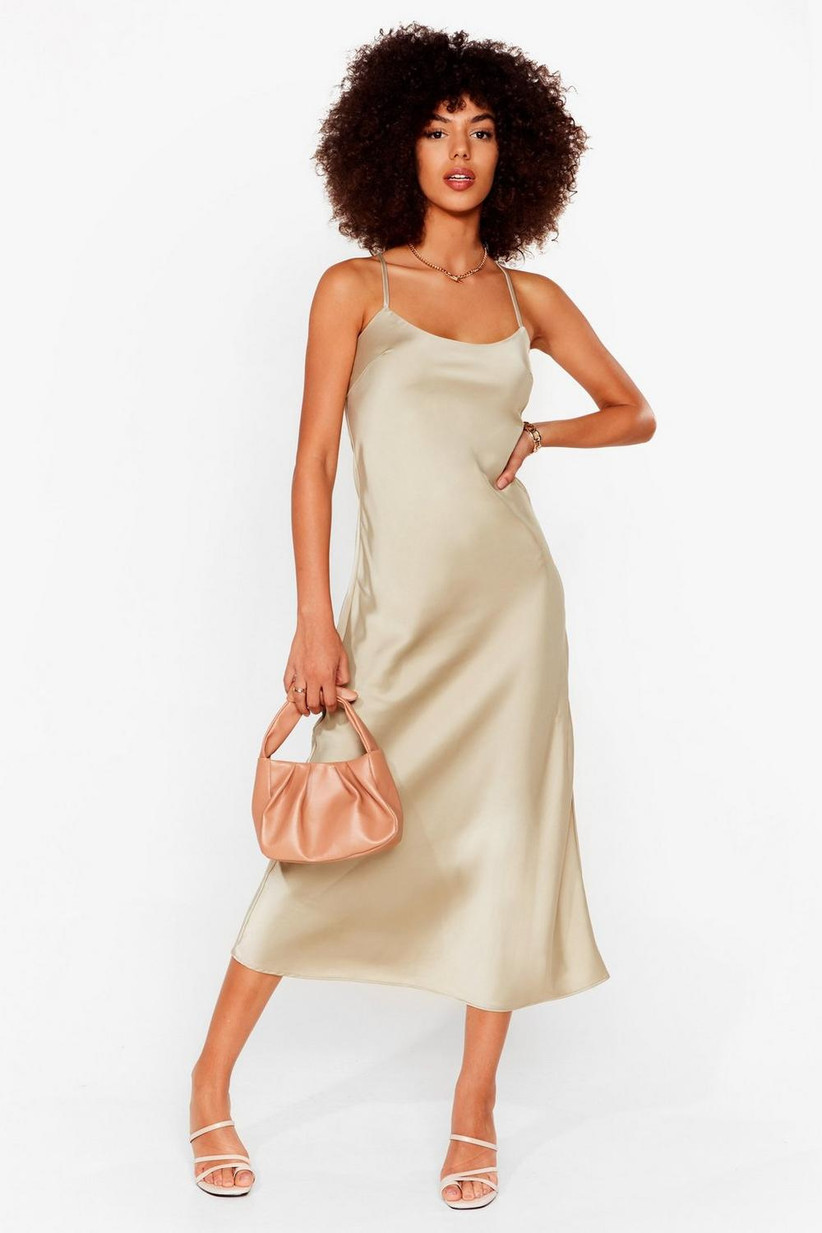 Girl wearing a cream satin slip dress with a nude bag