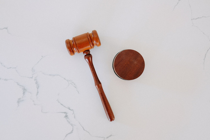 A wooden gavel shot from above on a white marble background