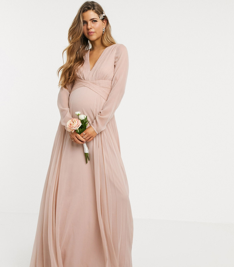 Pregnant woman wearing a long sleeve rose coloured dress