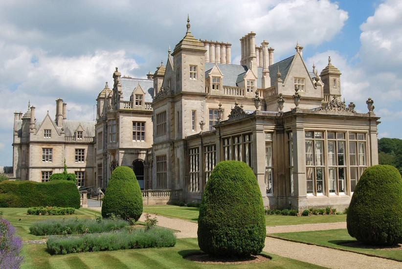 Outside view of a grand manor house with manicured hedges